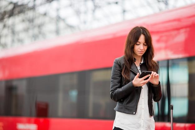 Vrouw met bagage bij station dat door trein reist. jonge toerist die met cellphone en bagage op platform op uitdrukkelijk wachten