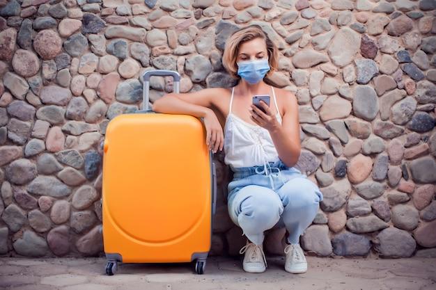 Vrouw met bagage die medische gezichtsmasker draagt en smartphone buiten gebruikt. reis- en coronavirus-concept