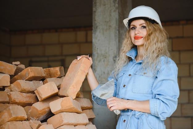 Vrouw met baksteen in bouwconcept