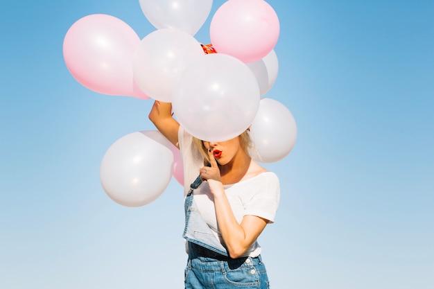 Vrouw met ballonnen gesturing stilte