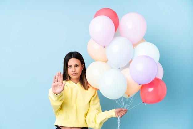 Vrouw met ballonnen in een partij stop gebaar met haar hand maken