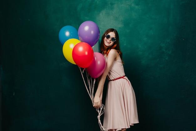 Vrouw met ballonnen in haar handen in een jurk, studio