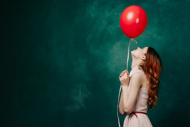 Vrouw met ballonnen in haar handen in een jurk