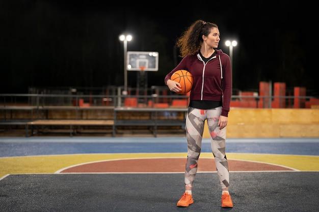 Vrouw met basketbal buitenshuis volledig schot