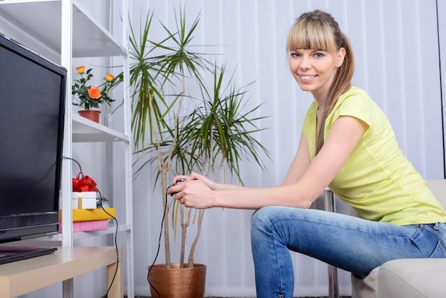 Vrouw met bedieningshendel het spelen videospelletjes thuis.
