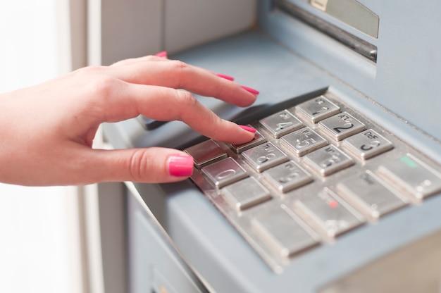 Vrouw met behulp van bankautomaat. detailopname