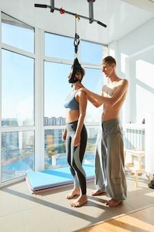 Vrouw met behulp van cervicale tractie-apparaat in yogastudio