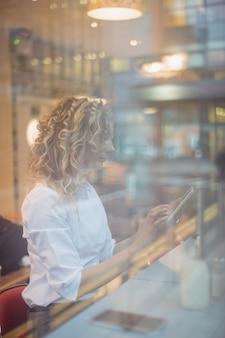 Vrouw met behulp van digitale tablet aan balie
