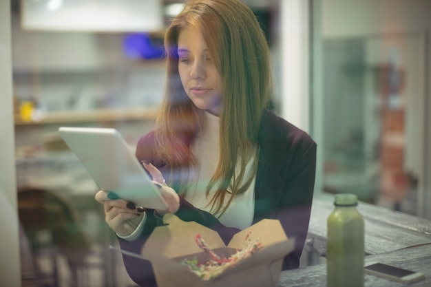 Vrouw met behulp van digitale tablet tijdens het eten van salade