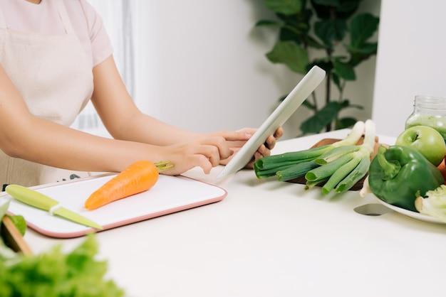 Vrouw met behulp van een digitale tablet in de keuken
