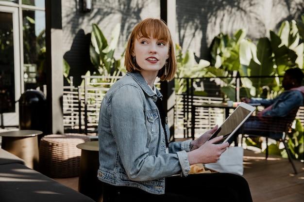 Vrouw met behulp van een digitale tablet in een café