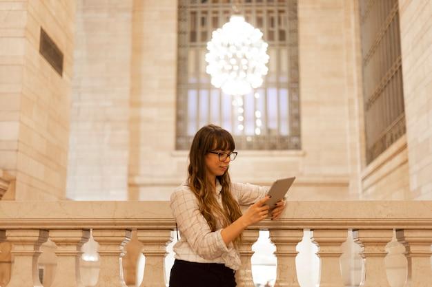 Vrouw met behulp van een digitale tablet in grand central terminal