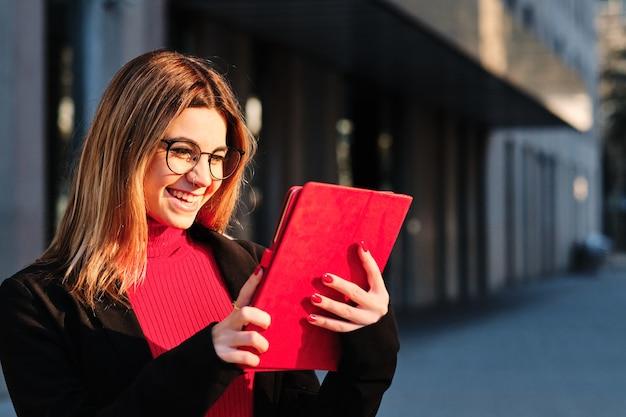 Vrouw met behulp van een digitale tablet terwijl ze buiten staat.