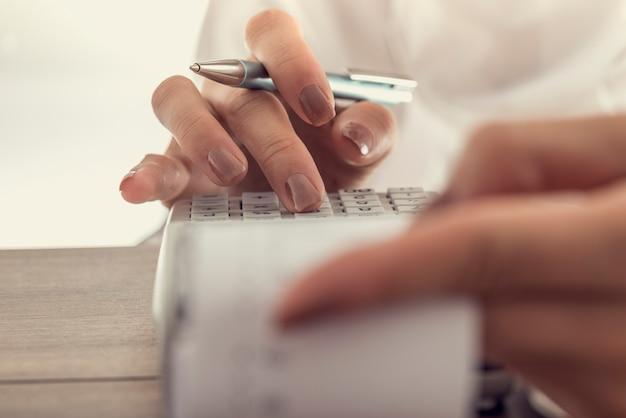 Vrouw met behulp van een handmatige rekenmachine om de rekeningen in het kantoor, vintage effect getinte afbeelding te doen.