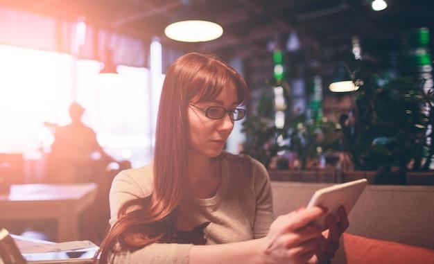 Vrouw met behulp van een mobiele telefoon in restaurant, café, bar