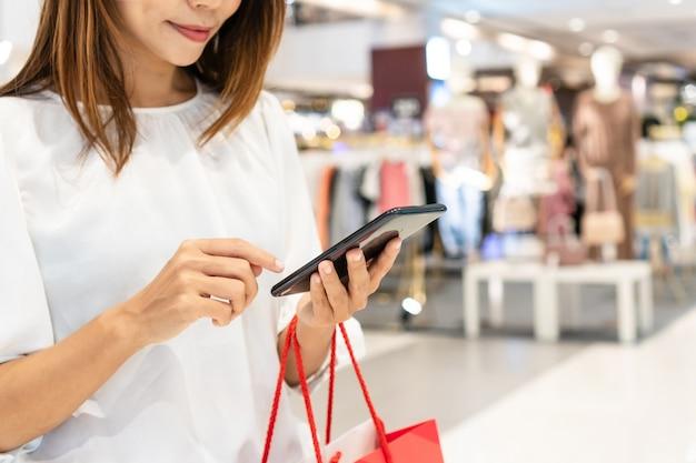 Vrouw met behulp van een mobiele telefoon terwijl ze boodschappentas