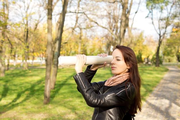 Vrouw met behulp van een opgerolde krant die tegen haar oog wordt gehouden om over een afstand te spioneren terwijl ze buiten in een park staat