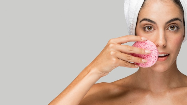 Vrouw met behulp van een roze spons kopie ruimte