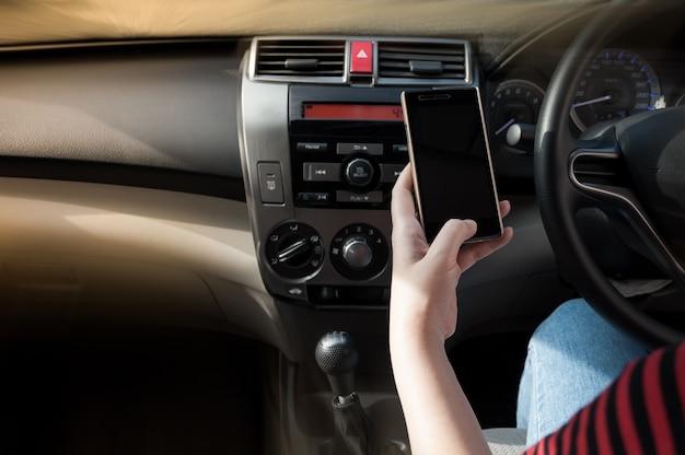 Vrouw met behulp van een smartphone tijdens het autorijden tussen autorijden omdat verslaafde sociale media