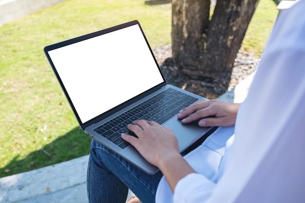 Vrouw met behulp van en typen op laptop met leeg wit scherm zitten in het park