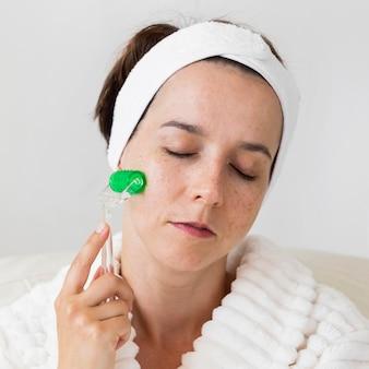 Vrouw met behulp van haar hoofdband en het gezicht close-up masseren