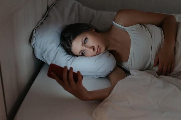 Vrouw met behulp van haar smartphone in bed 's nachts in plaats daarvan slapen