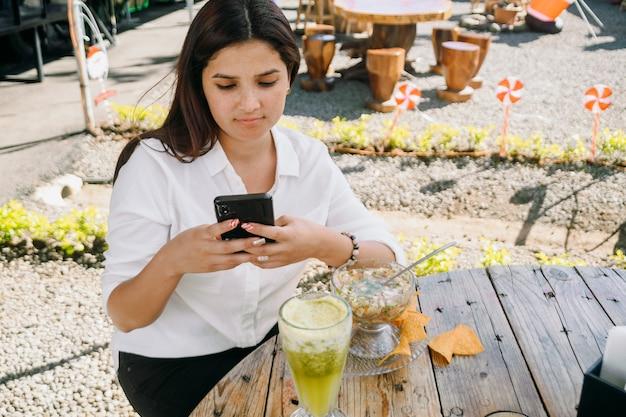 Vrouw met behulp van haar telefoon en eten in een restaurant