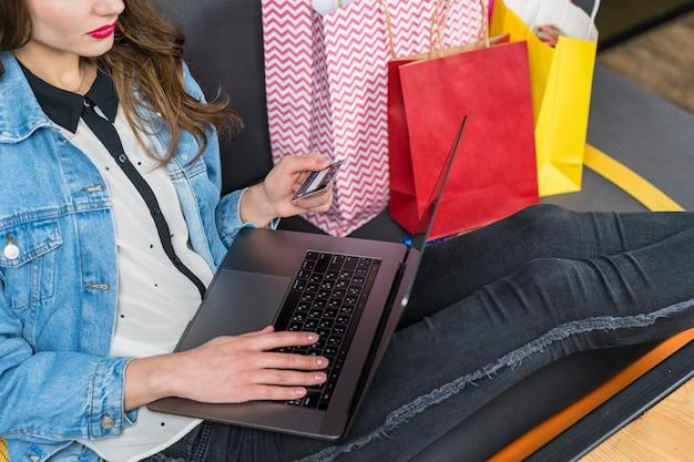Vrouw met behulp van laptop en creditcard voor online winkelen