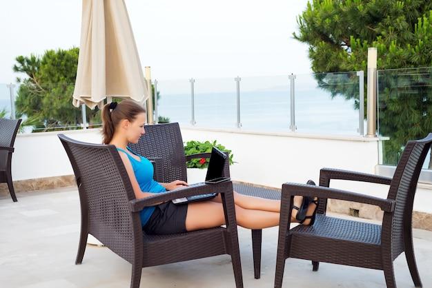 Vrouw met behulp van laptop met zwarte leeg scherm mock-up in straat café met uitzicht op de zee