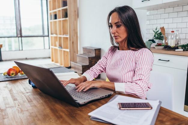 Vrouw met behulp van laptop zittend in de keuken en die op laptop werkt.