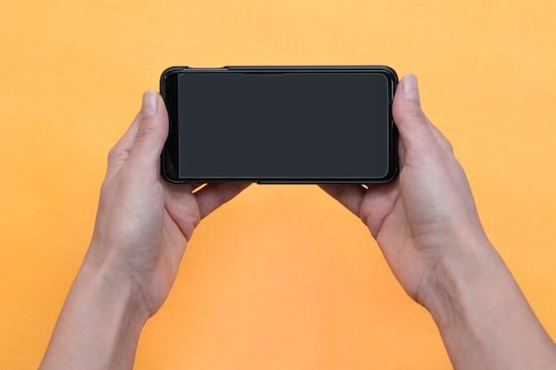 Vrouw met behulp van mobiele slimme telefoon geïsoleerd op een oranje achtergrond.