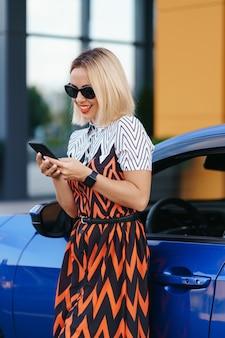 Vrouw met behulp van mobiele telefoon, communicatie of online applicatie, staande in de buurt van auto op straat of parkeren, buitenshuis. autodelen, verhuur