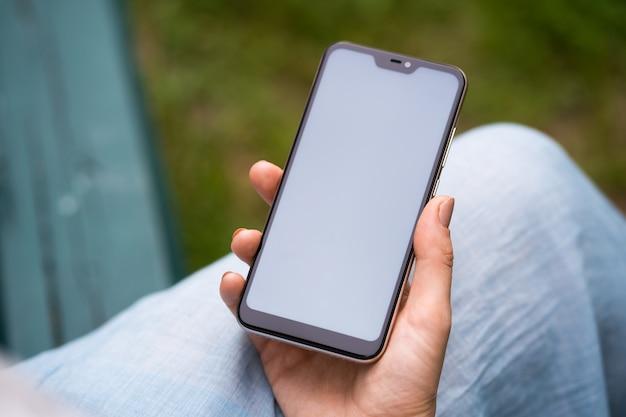 Vrouw met behulp van mobiele telefoon en scherm met vinger aan te raken, mockup voor app-ontwerp.