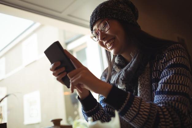 Vrouw met behulp van mobiele telefoon in de buurt van venster