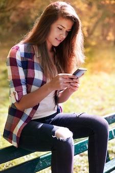 Vrouw met behulp van mobiele telefoon in het park