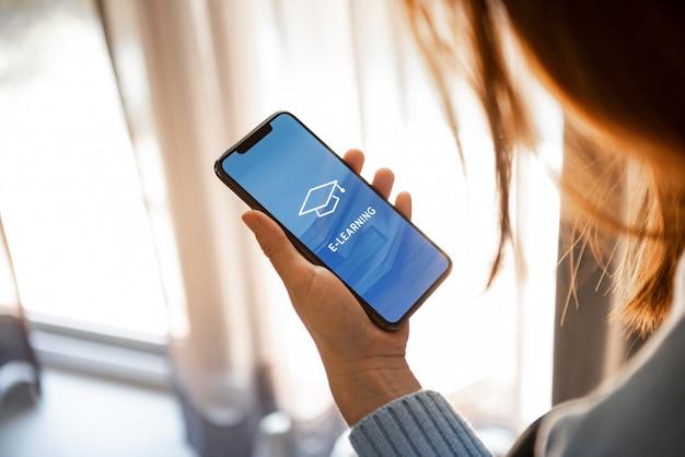 Vrouw met behulp van mobiele telefoon met inscriptie op scherm e-learning.