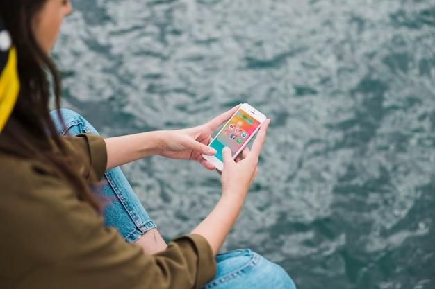 Vrouw met behulp van mobiele telefoon met sociale media meldingen op het scherm
