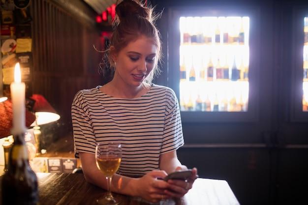 Vrouw met behulp van mobiele telefoon met wijn op tafel