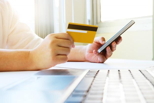 Vrouw met behulp van mobiele telefoon om online winkelen en te betalen met credit ca