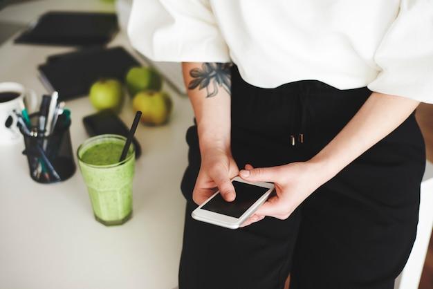 Vrouw met behulp van mobiele telefoon op kantoor aan huis
