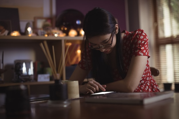 Vrouw met behulp van mobiele telefoon op tafel