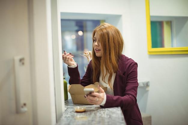 Vrouw met behulp van mobiele telefoon tijdens het eten van salade