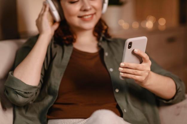 Vrouw met behulp van moderne hoofdtelefoons en smartphoneapparaat thuis op de bank