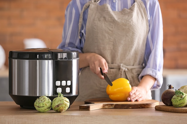 Vrouw met behulp van moderne multi-fornuis in de keuken