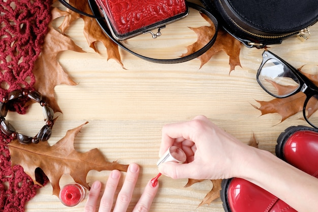 Vrouw met behulp van nagellak op houten tafel met accessoires en herfstbladeren
