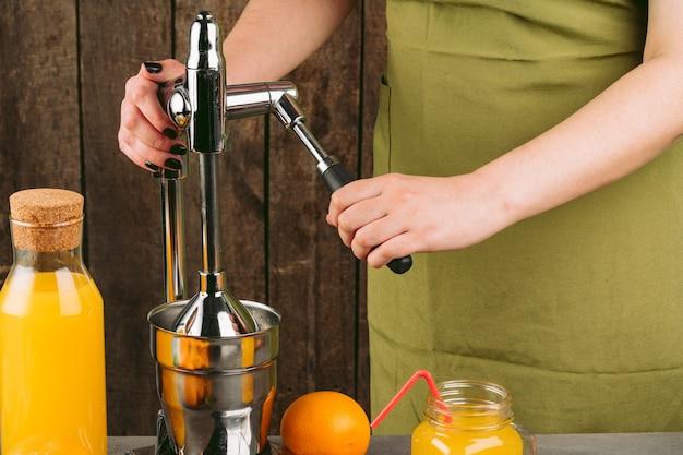 Vrouw met behulp van oranje juicer-apparaat thuis
