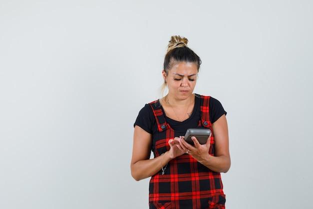 Vrouw met behulp van rekenmachine in overgooier jurk en op zoek naar drukke, vooraanzicht.