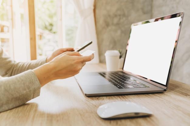 Vrouw met behulp van slimme telefoon en creditcard om online te winkelen in de coffeeshop