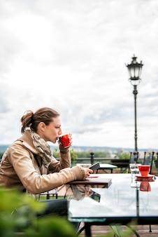 Vrouw met behulp van slimme telefoon en koffie drinken
