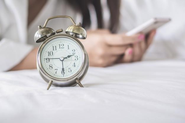 Vrouw met behulp van slimme telefoon laat op bed